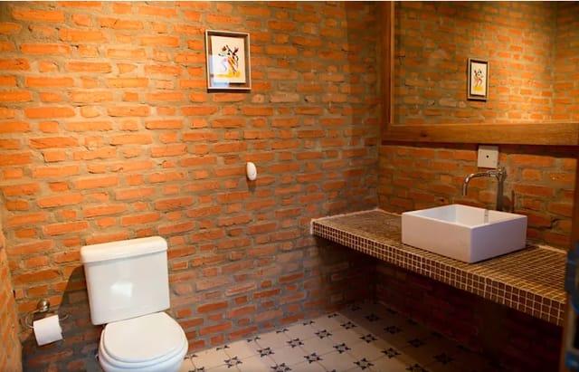 banheiro com tijolos tom terroso